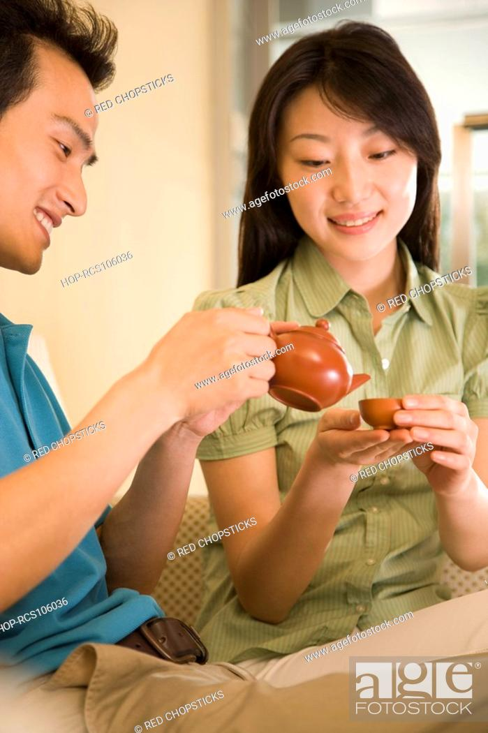 Stock Photo: Young man pouring tea into a cup held by a young woman.