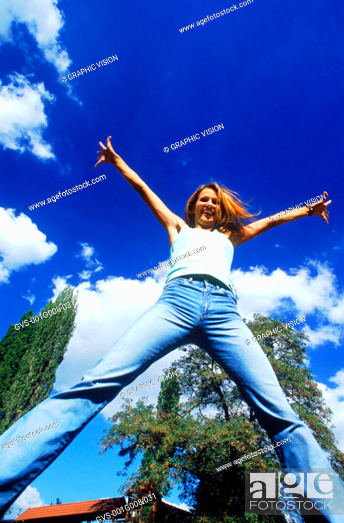 Stock Photo: Low angle view of a young woman jumping.