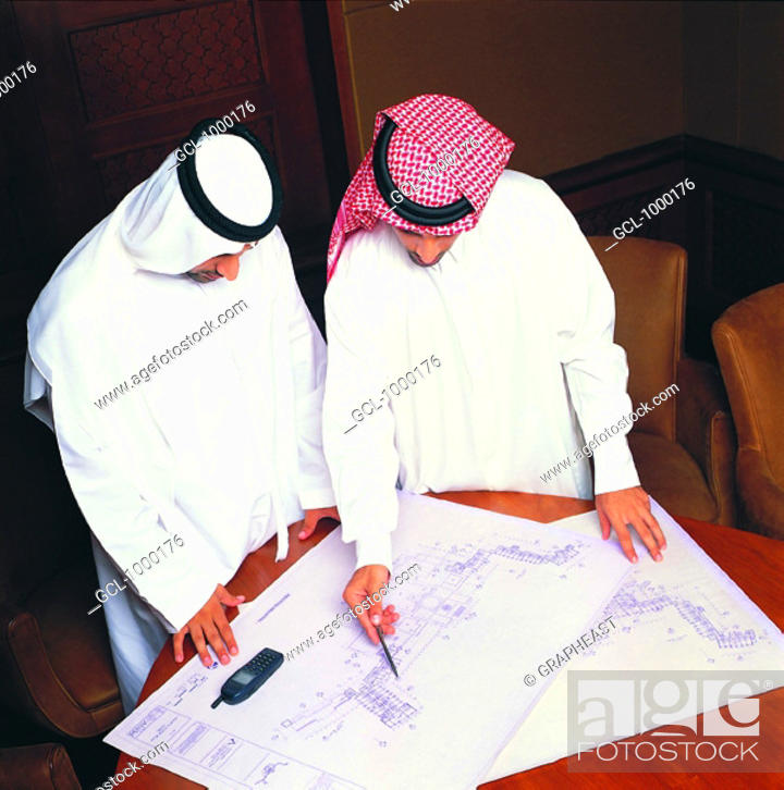 Stock Photo: Arab businessmen discussing architectural sketches.