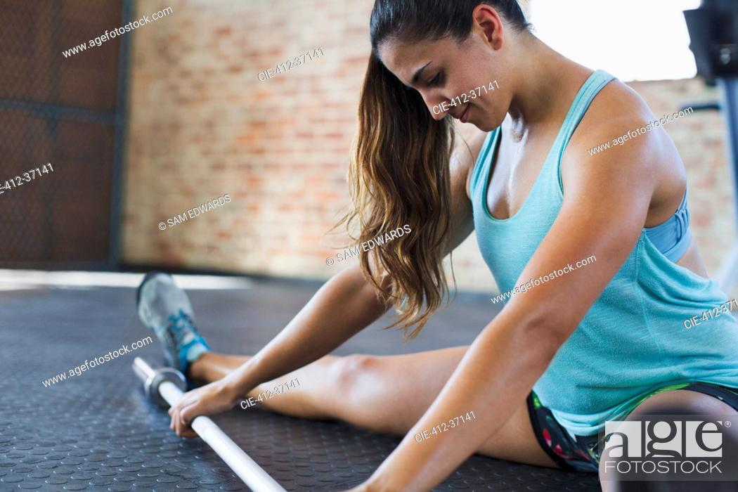 Stock Photo: Focused young woman stretching leg, using barbell in gym.