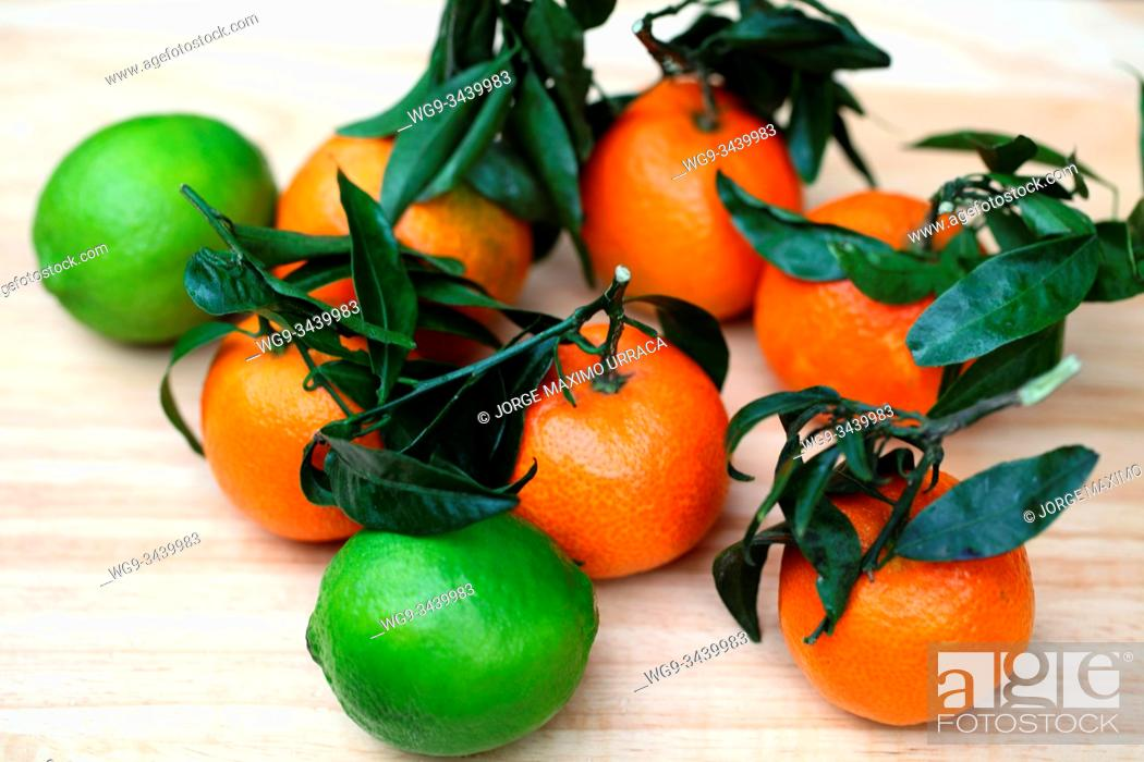 Stock Photo: Tangerines and limes on wooden board.