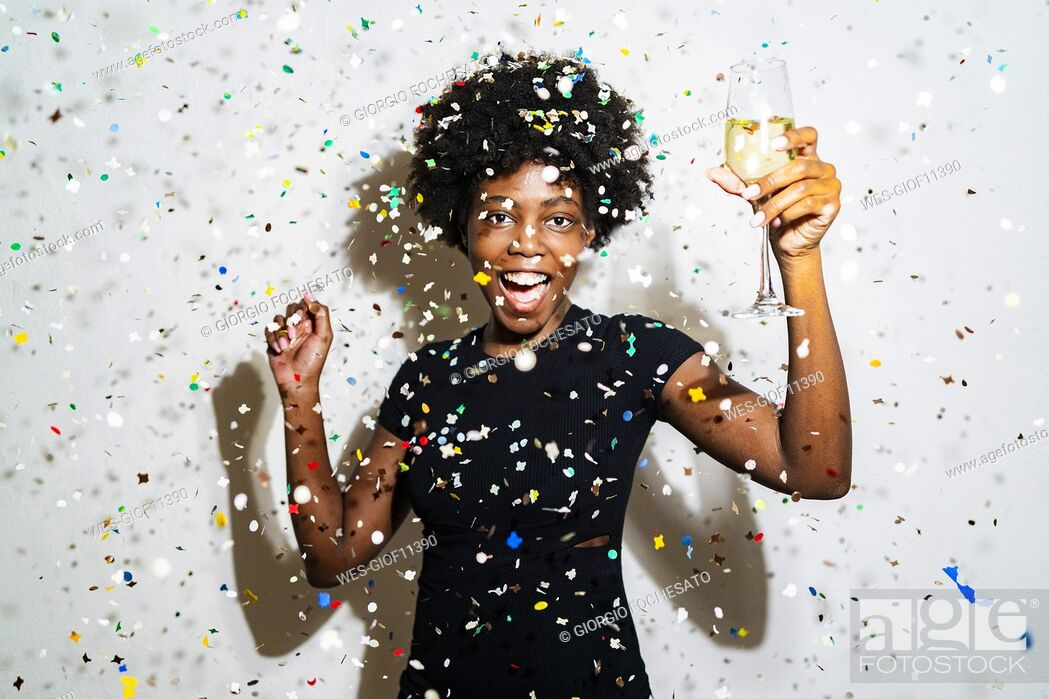 Stock Photo: Happy woman with champagne flute dancing while standing amidst confetti against white background.