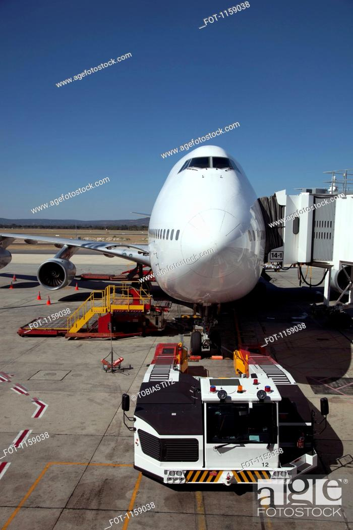 Stock Photo: Jumbo jet attached to boarding bridge with tug in front.