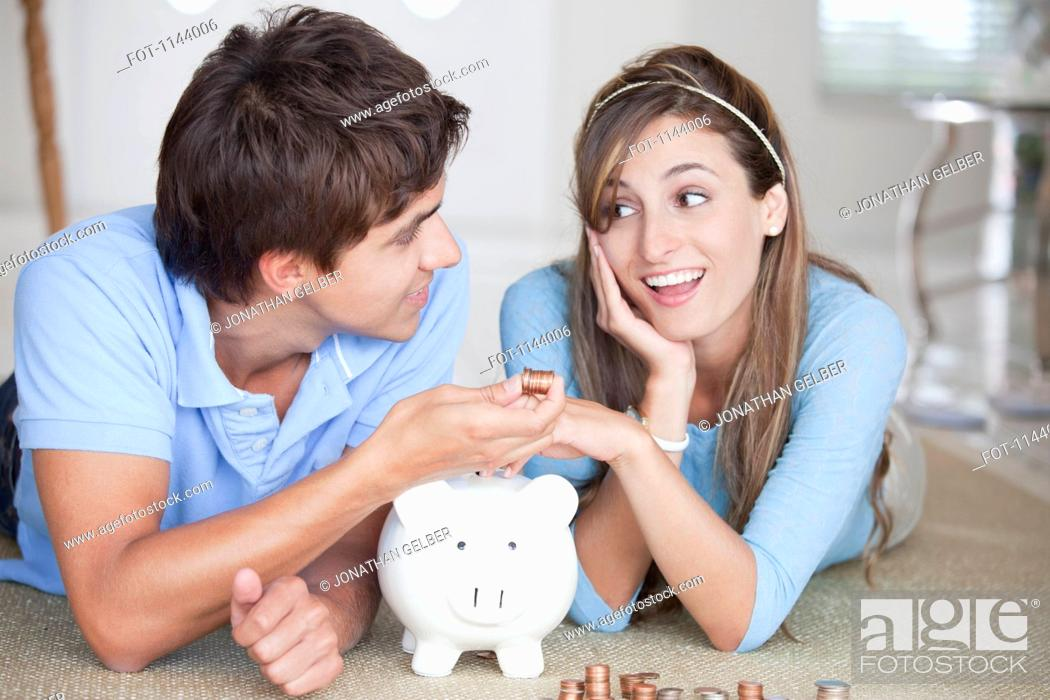 Stock Photo: A young couple lying on the floor counting coins.