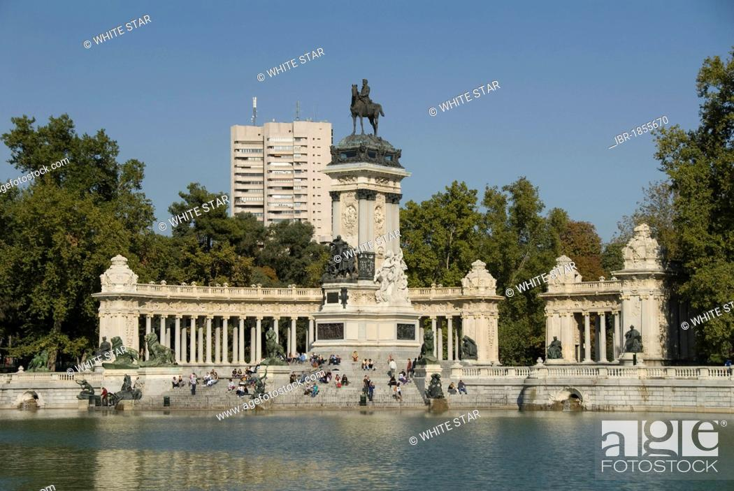 Photo de stock: View over an artificial lake towards people in front of a monument with an equestrian statue of King Alfosno XII, Parque del Buen Retiro.