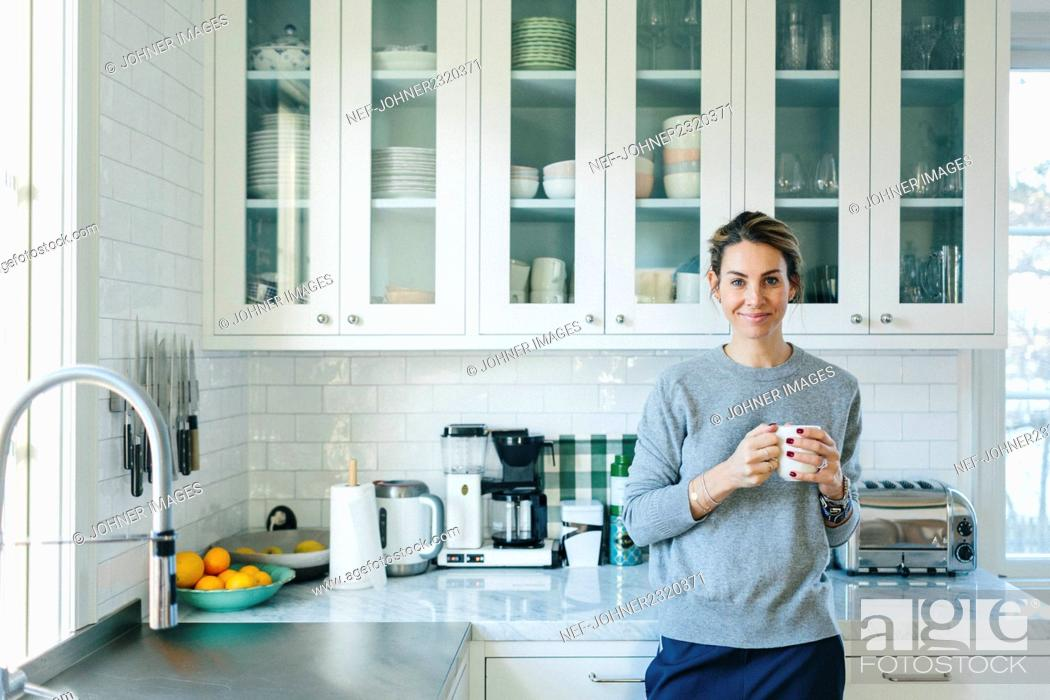 Stock Photo: Young woman drinking coffee at home.