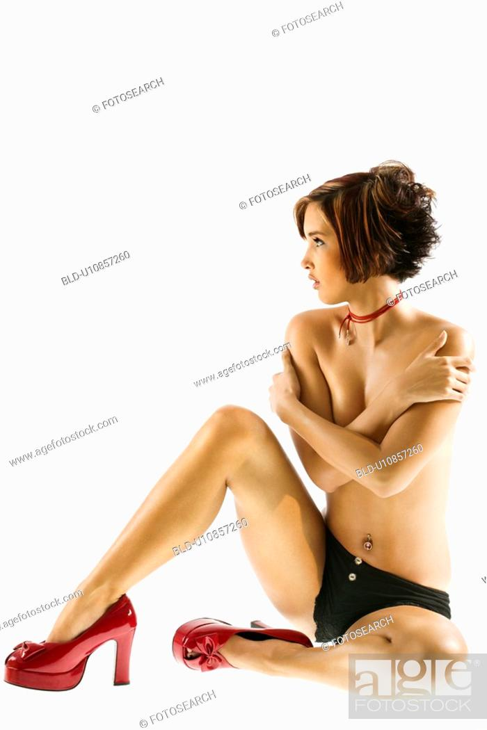 Stock Photo: Studio portrait of young partially nude Caucasian woman sitting with arms crossed over chest.