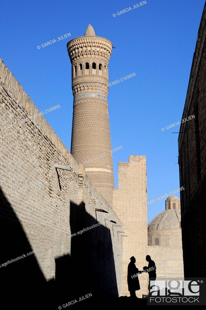 Stock Photo: Uzbekistan, Bukhara, historic centre listed as World Heritage by UNESCO, silhouette of two men shaking hands in a small street near Kalon minaret.