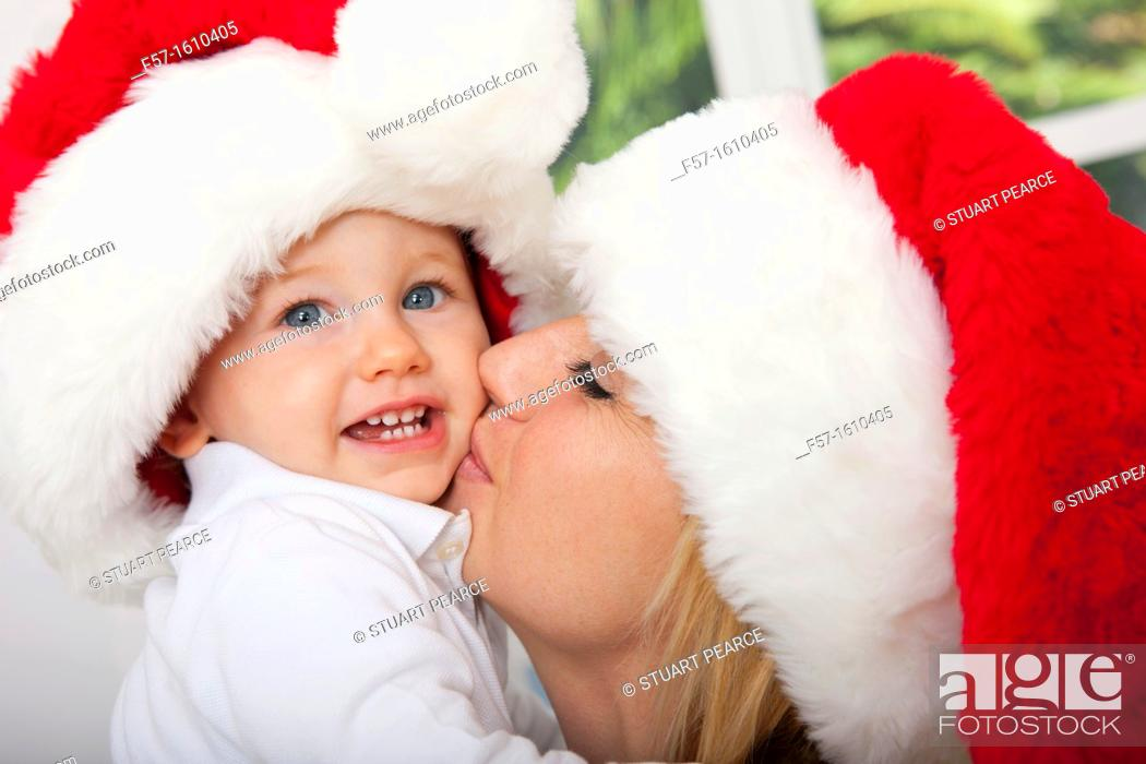 Stock Photo: Mother and child wearing Santa hats.