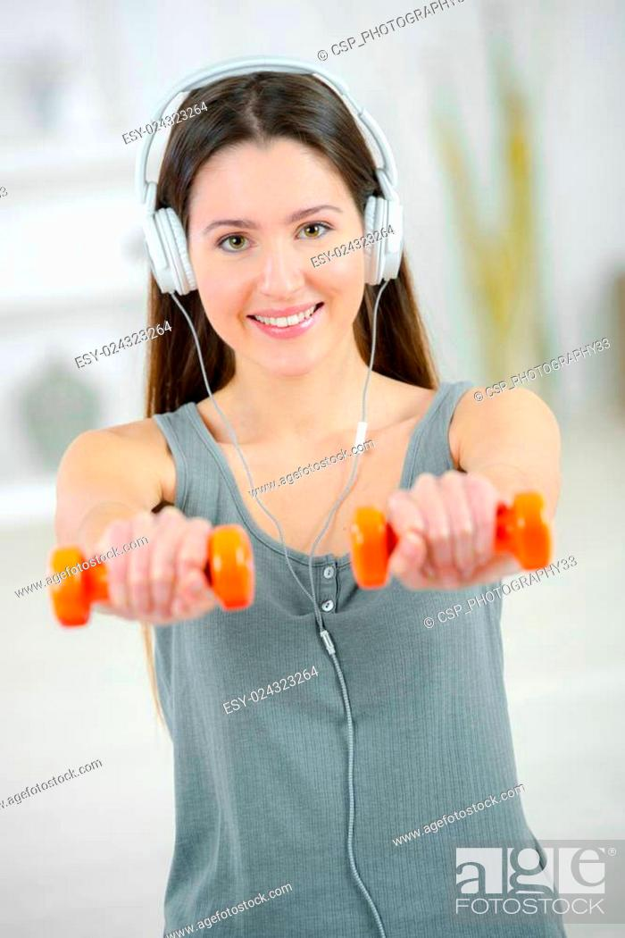 Stock Photo: Woman lifting weights whilst listening to music.