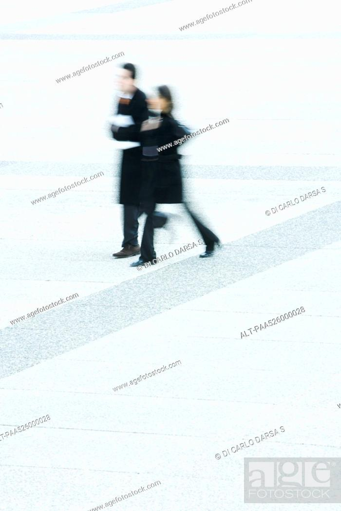 Stock Photo: Businessman and businesswoman walking together across public square.