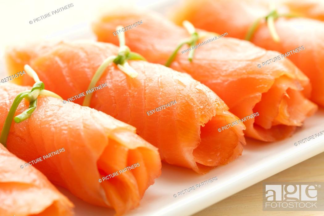 Photo de stock: Rolls of smoked salmon with chives as a snack.