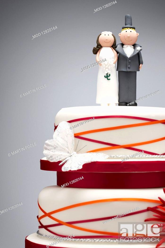 Stock Photo: Comical bride and groom figurines on top of wedding cake.