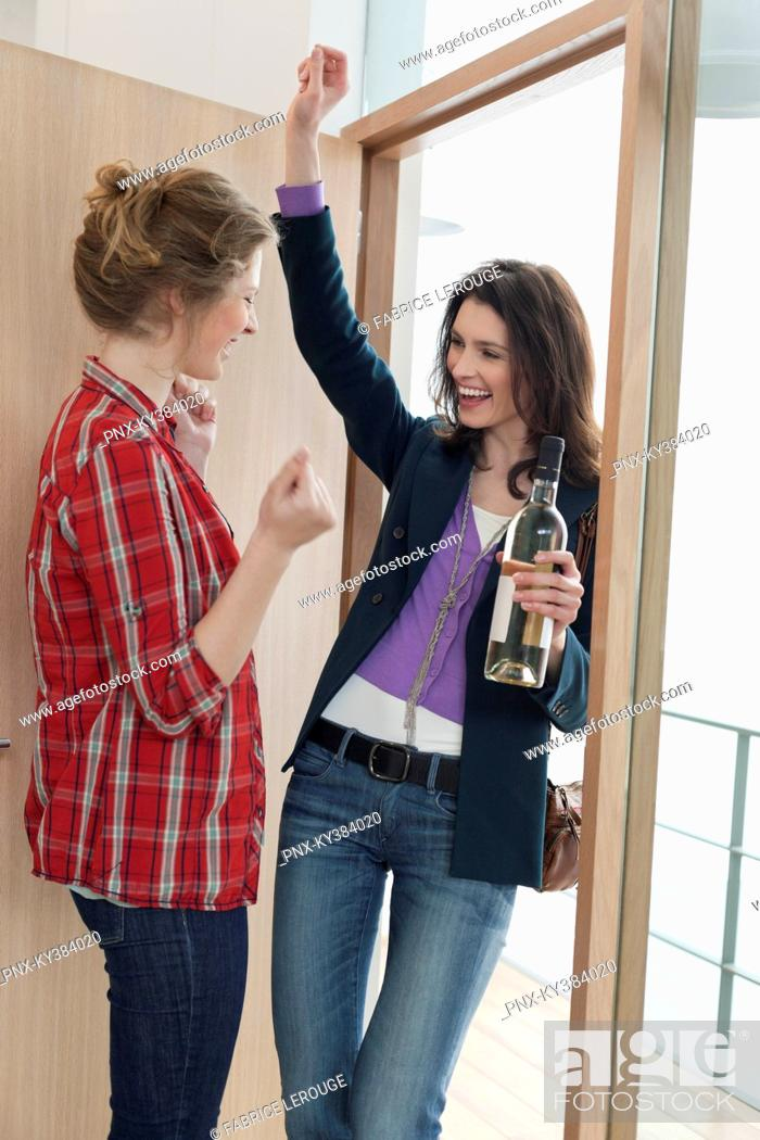 Stock Photo: Woman arriving at her friends home with a wine bottle.