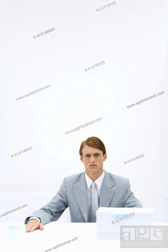 Stock Photo: Businessman sitting at table with two different sized stacks of paper.