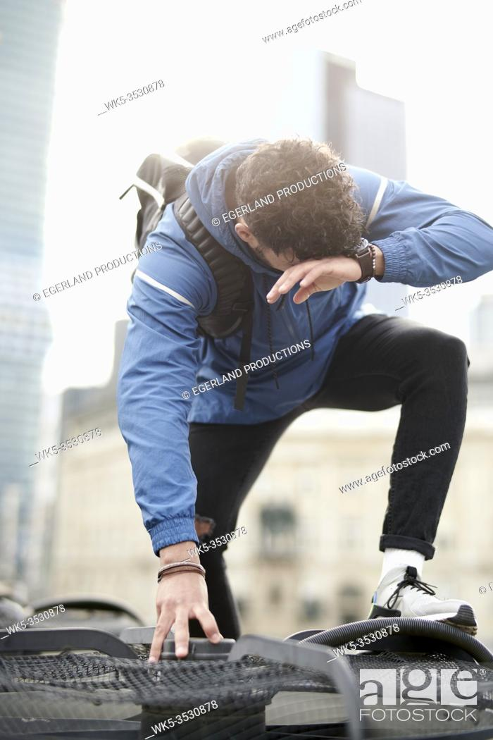 Stock Photo: Young sportsman climbing on rooftop in Frankfurt am Main, Germany.