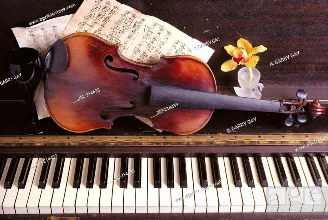 Old violin on piano with sheet music and orchids, Stock