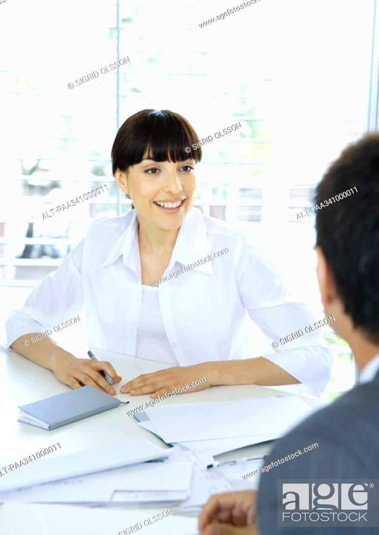 Stock Photo: Businesswoman talking to colleague across table.