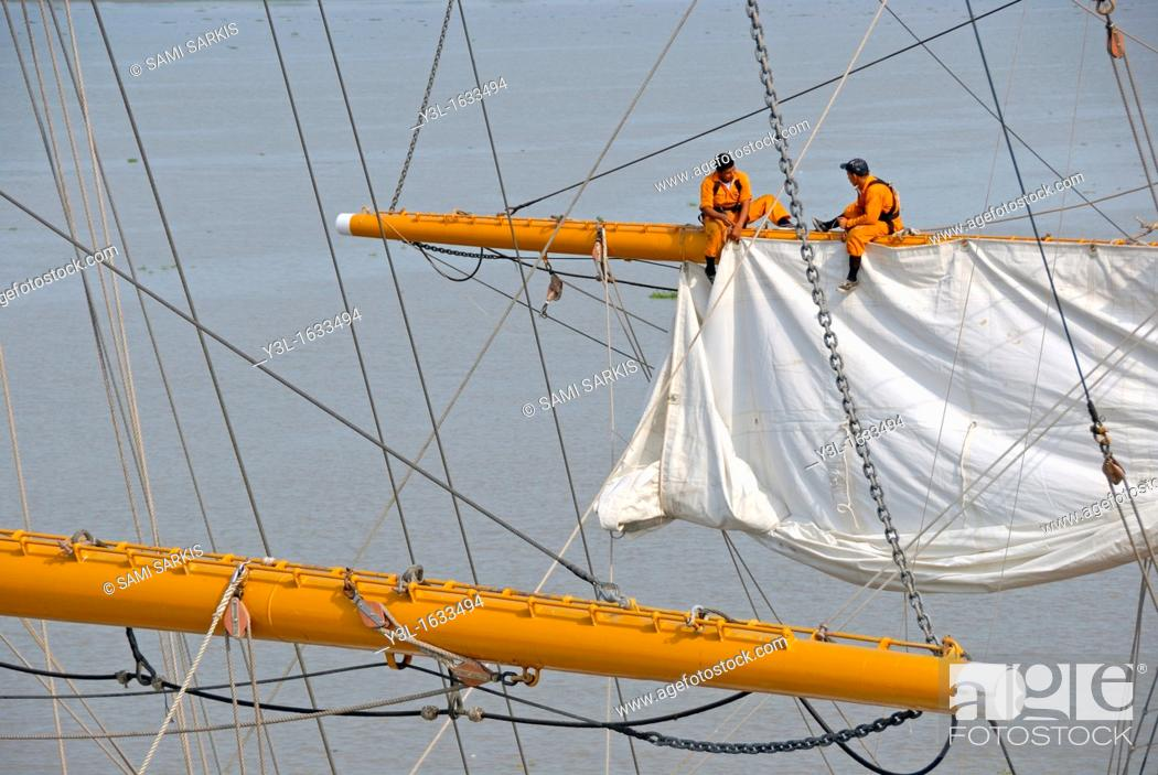 Stock Photo: Men repairing a sail of the three-masted sailboat on Guayas river, used as a training ship for Ecuadorian Navy cadets, Guayaquil, Ecuador.