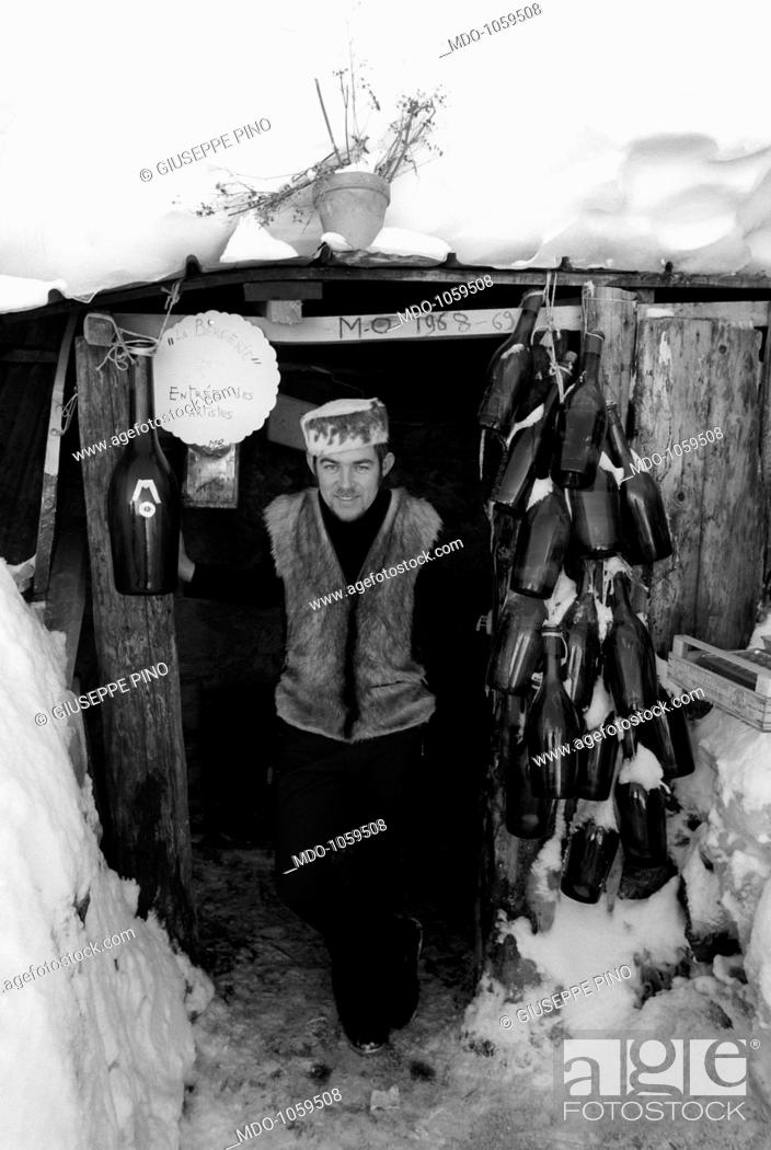 Imagen: A shepherd. A shepherd at the entrance of a farm building on which frames are hung many glass bottles. Sankt Moritz, March 1969.