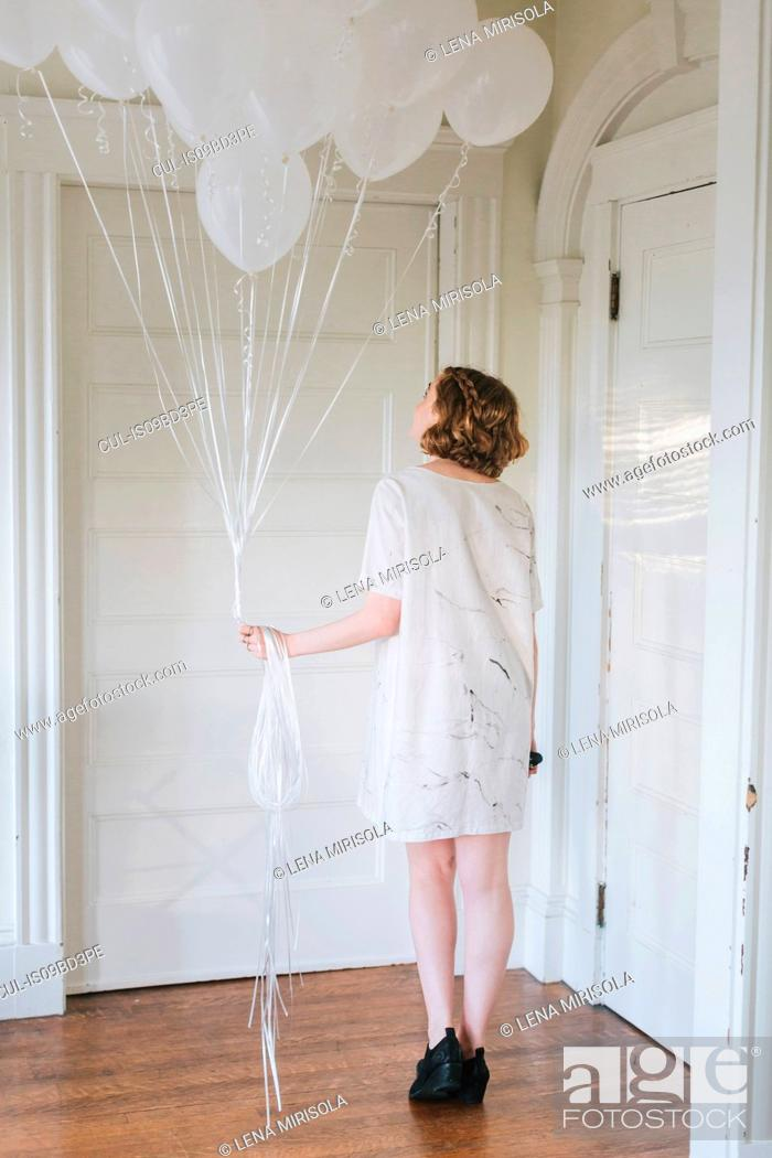 Photo de stock: Woman in apartment holding bunch of balloons, rear view.