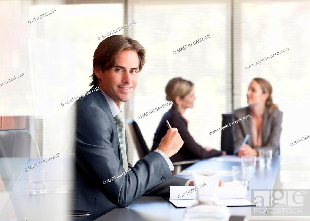 Stock Photo: Portrait of smiling businessman in conference room.
