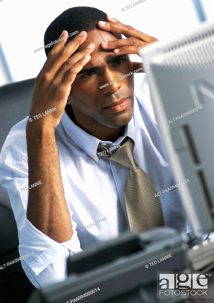 Stock Photo: Businessman holding head in hands.
