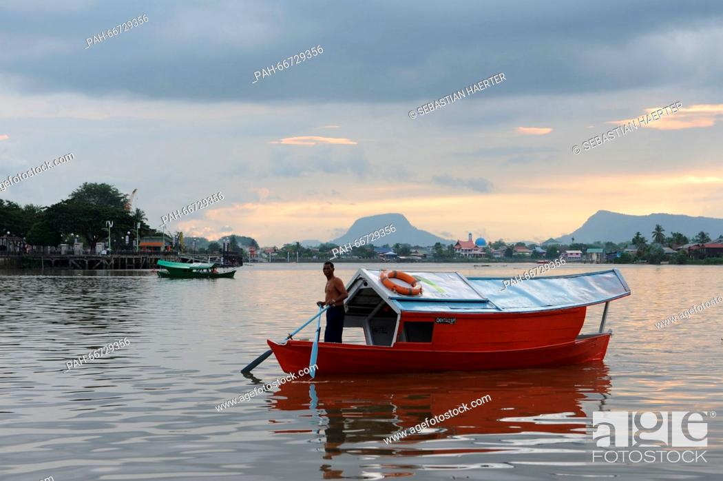 Stock Photo: A ferryman on a wooden boat on the Sarawak River in Kuching, Malaysia, 21 October 2014. Photo: Sebastian Kahnert | usage worldwide.