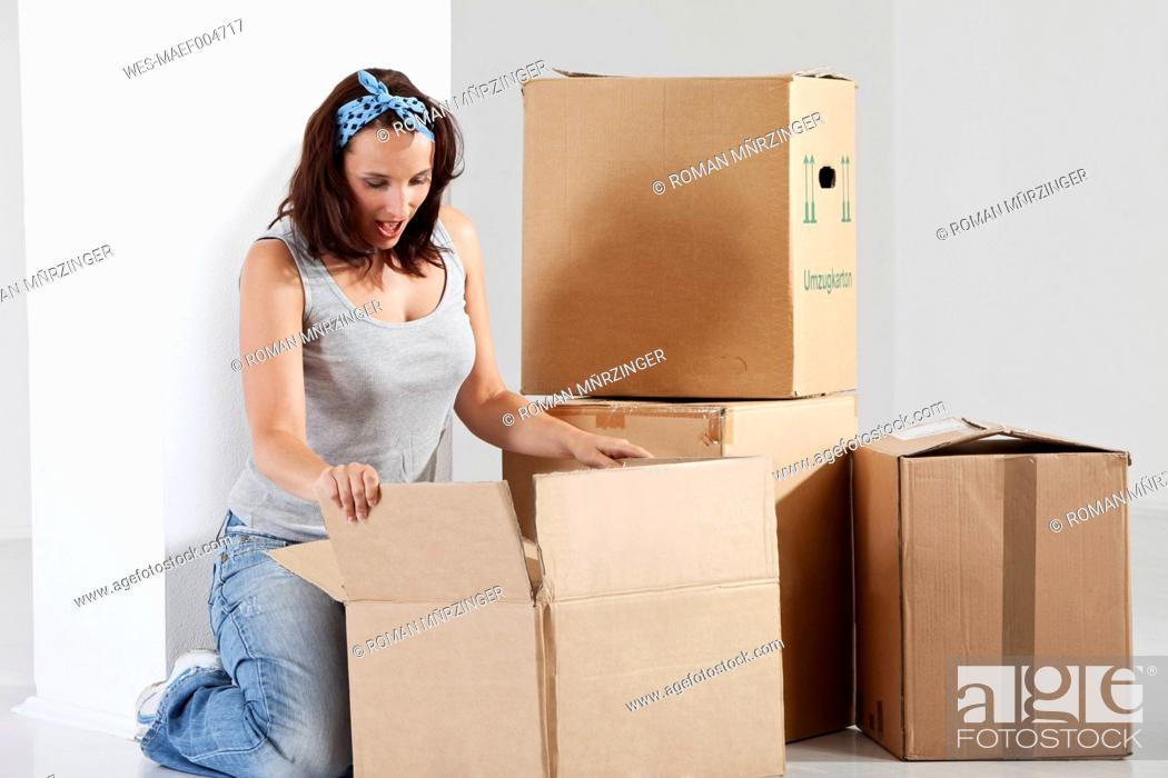 Stock Photo: Young woman opening box.