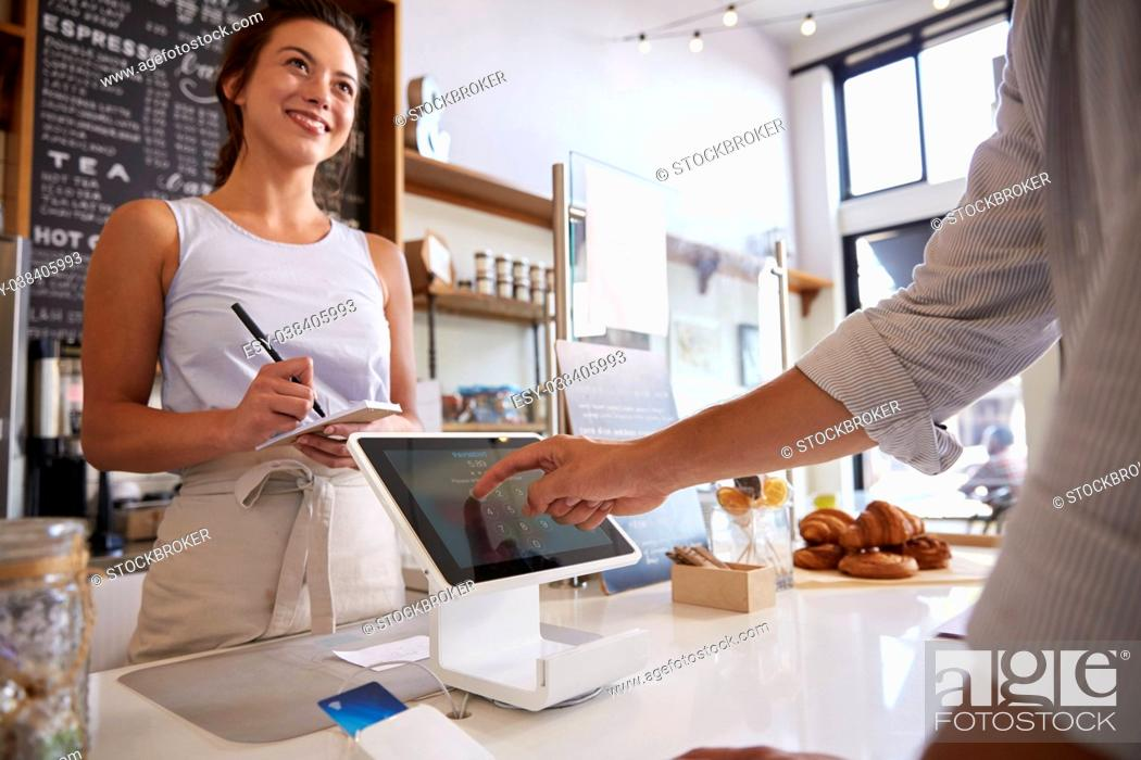 Stock Photo: Customer using touch screen to make payment at a coffee shop.