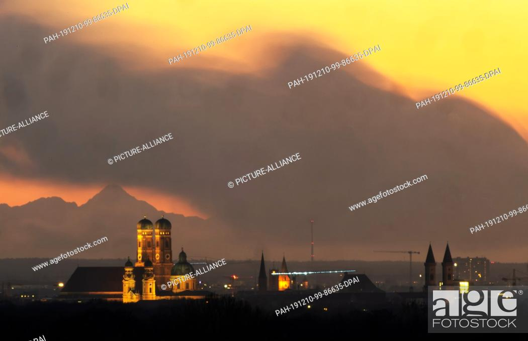 Stock Photo: 10 December 2019, Bavaria, Munich: The Allgäu Alpine panorama stands behind the backdrop of the illuminated Bavarian capital on a clear day.