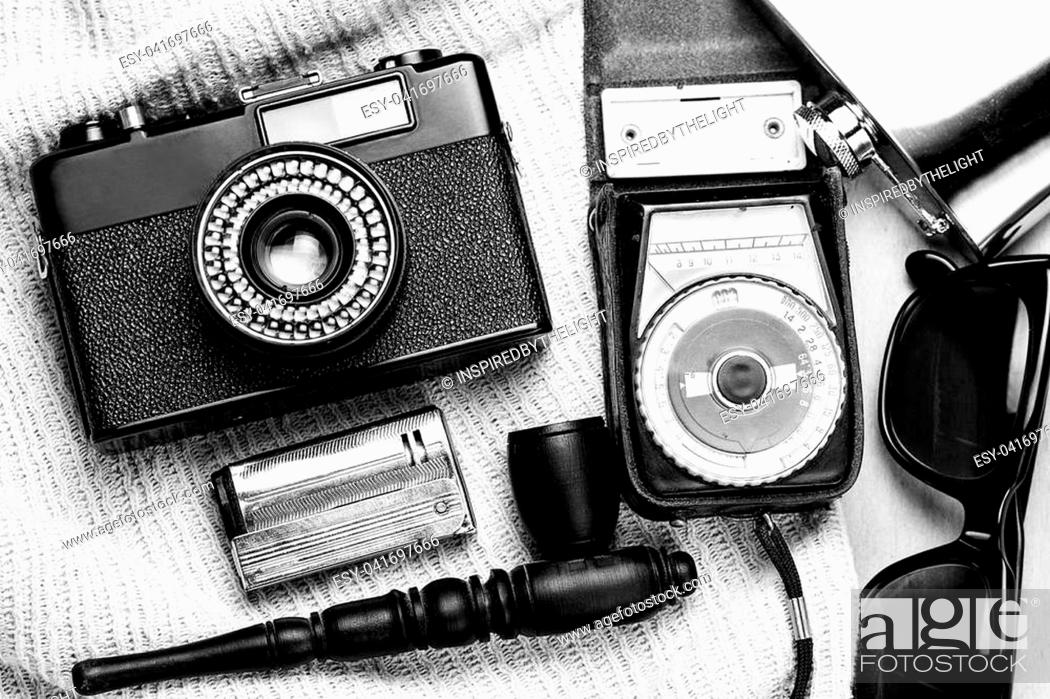Stock Photo: Accessories of the creative person. 35-mm film camera, exposure meter in leather case, steel flask, sunglasses and smoking set on wooden background.