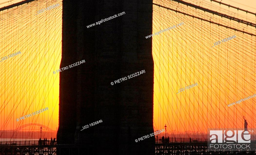 Stock Photo: New York City, the Liberty Statue seen in the distance, at dusk, through the Manhattan Bridge.