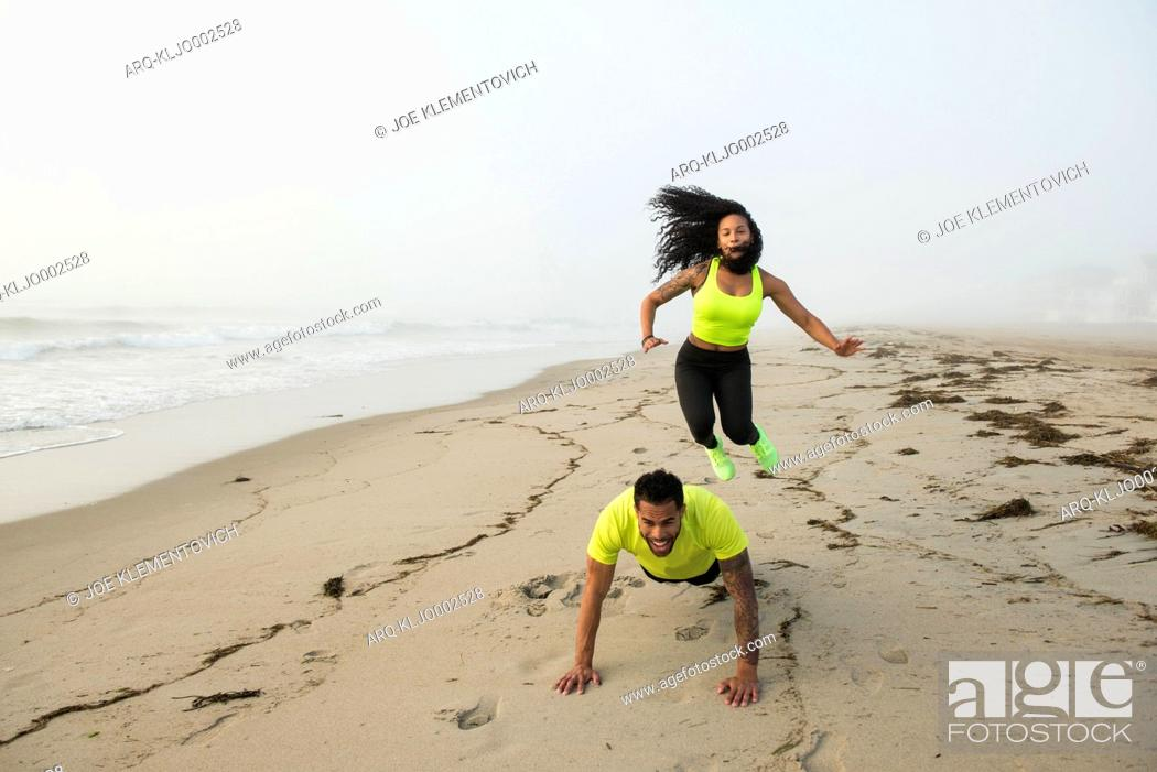 Imagen: Man and woman working out on sandy beach during foggy day, Hampton, New Hampshire, USA.
