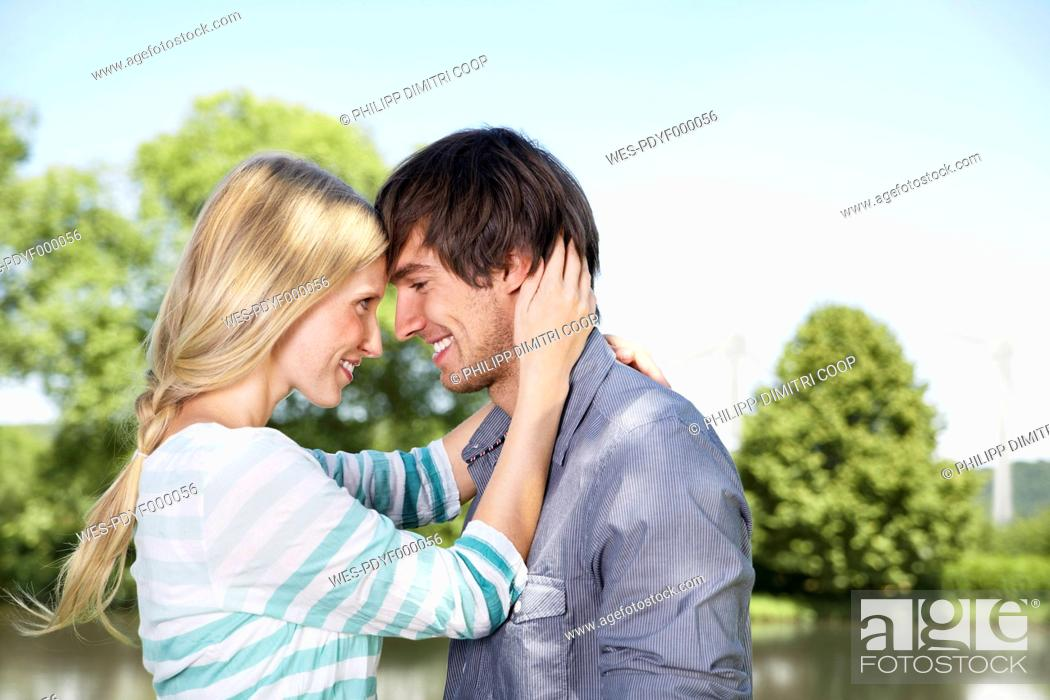 Stock Photo: Germany, Cologne, Young couple embracing, smiling.