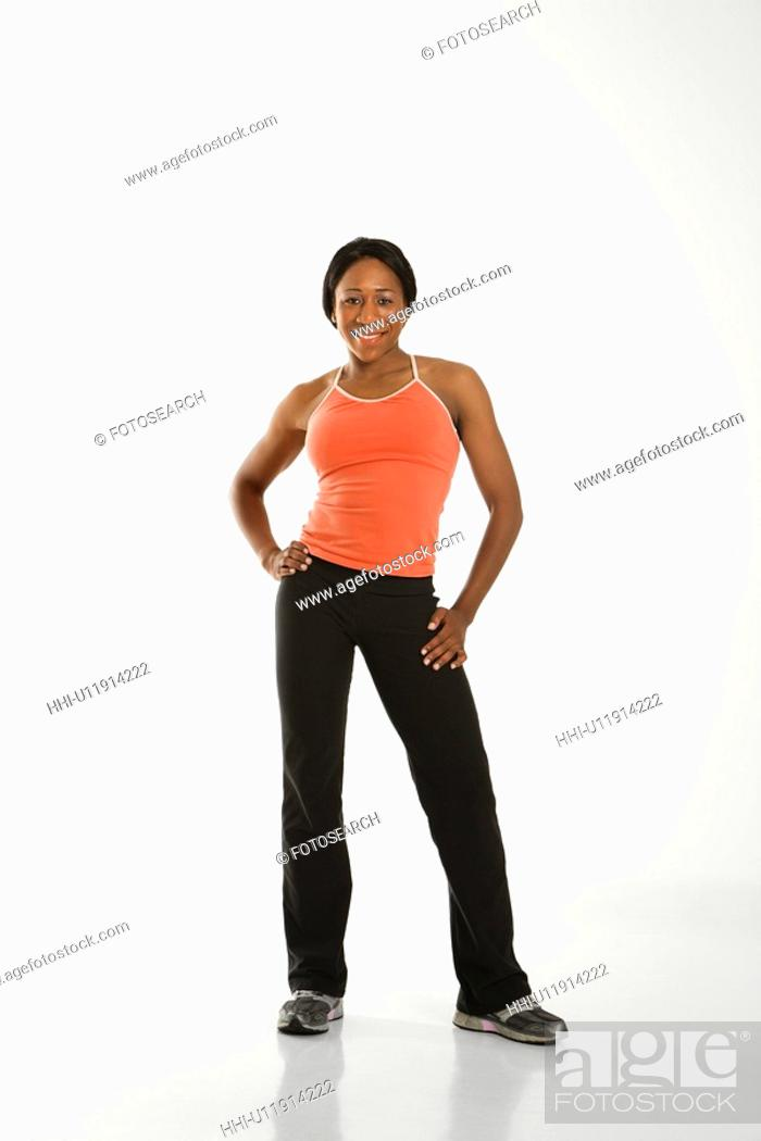 Stock Photo: African American young adult woman in athletic wear smiling at viewer with hands on hips.