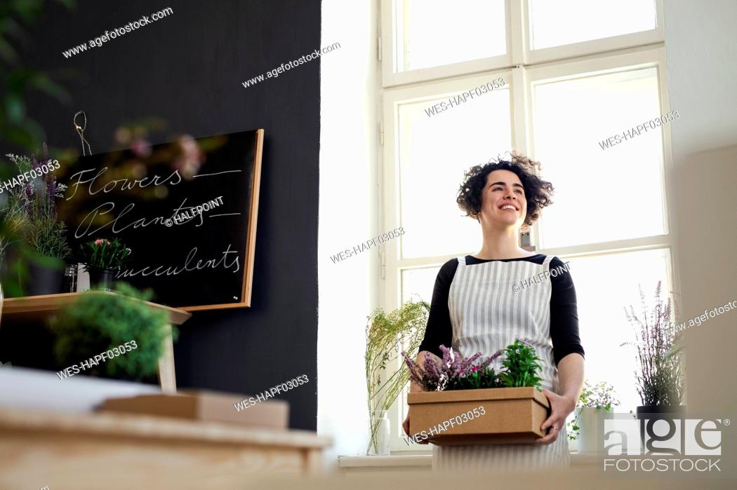 Stock Photo: Happy young woman holding flowers in a cardboard box in a small shop.