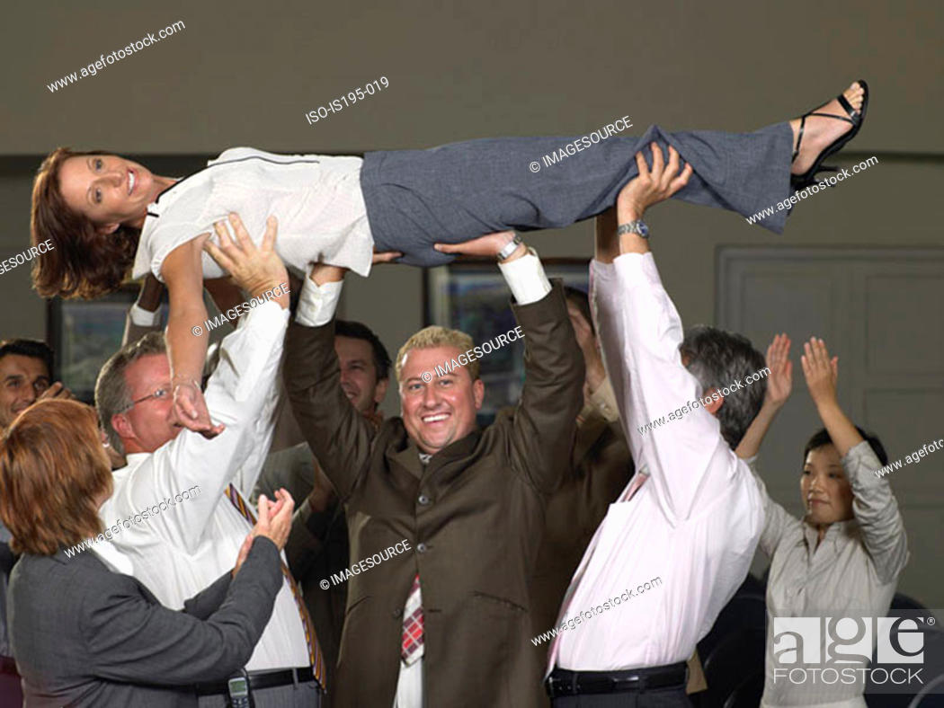 Stock Photo: Office workers lifting colleague up.