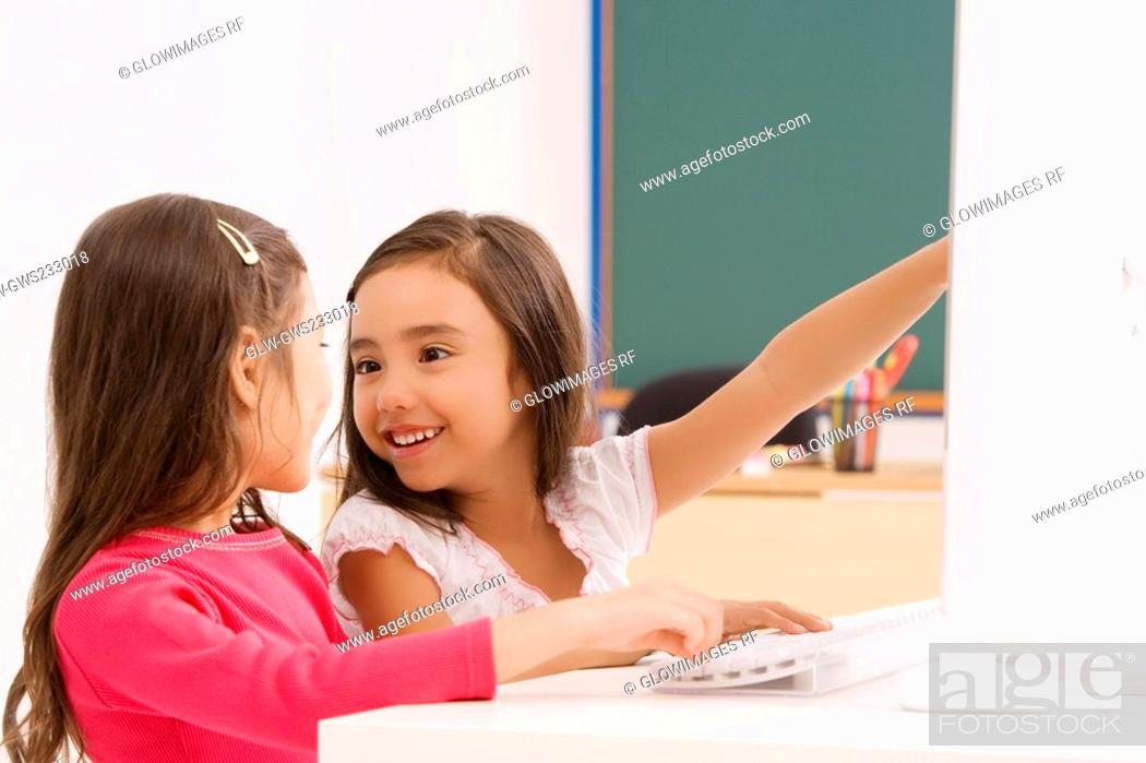 Stock Photo: Side profile of two schoolgirls smiling in front of a computer.