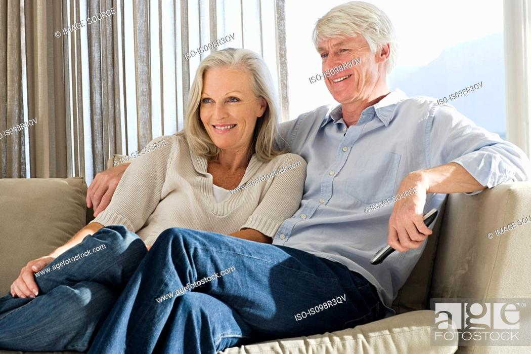 Stock Photo: Middle aged couple relaxing on couch together.