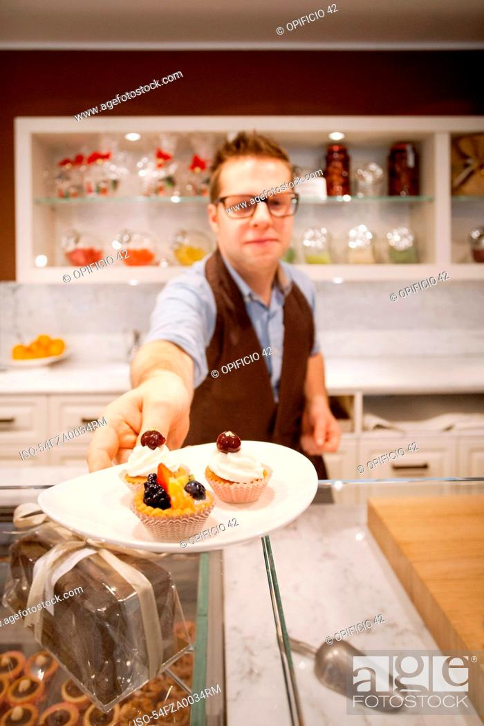 Stock Photo: Cashier holding plate of tarts in bakery.