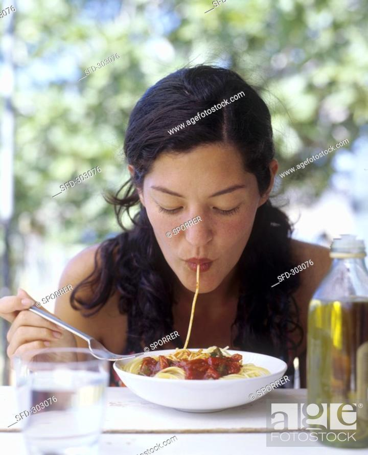 Imagen: A woman sucking spaghetti into her mouth.