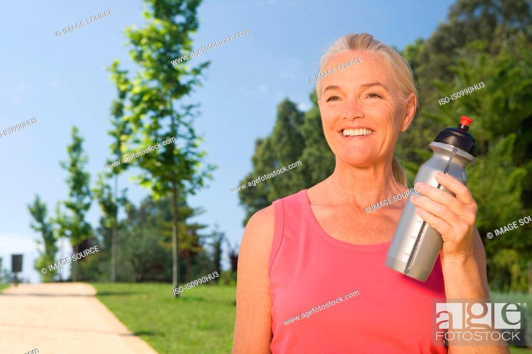 Stock Photo: Mature woman runner with water bottle.