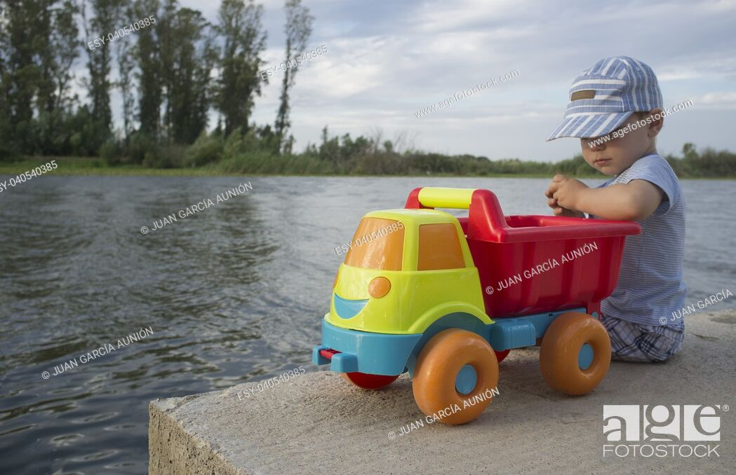 Imagen: Two year old boy playing at riverside with dump truck. He is sitting over fisher platform throwing stones.