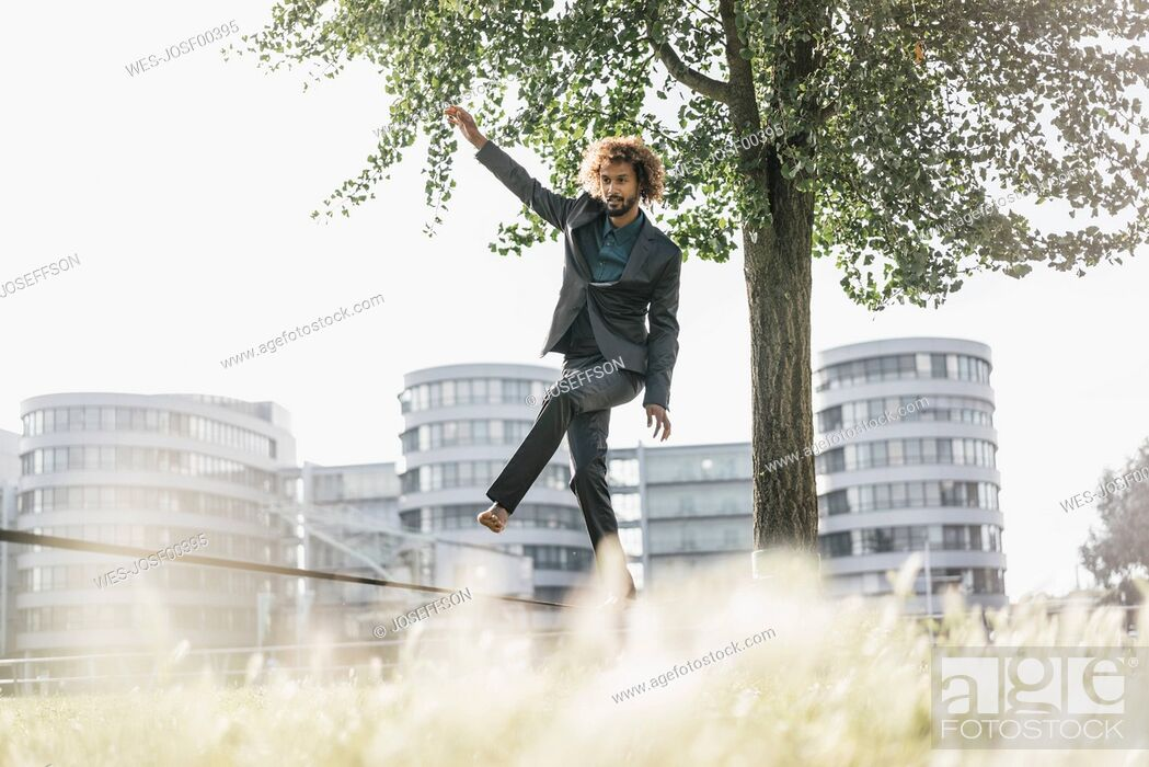 Stock Photo: Young businessman balancing on slackline.