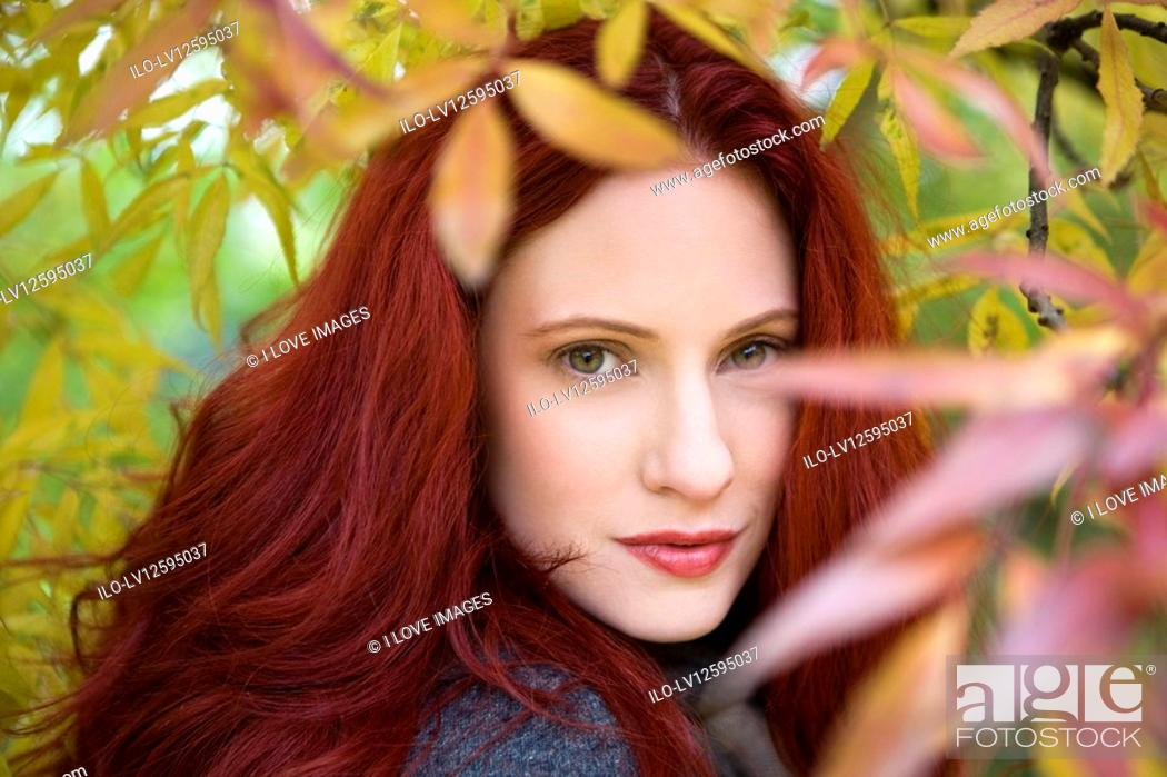 Stock Photo: A young woman standing under a tree in autumn time.