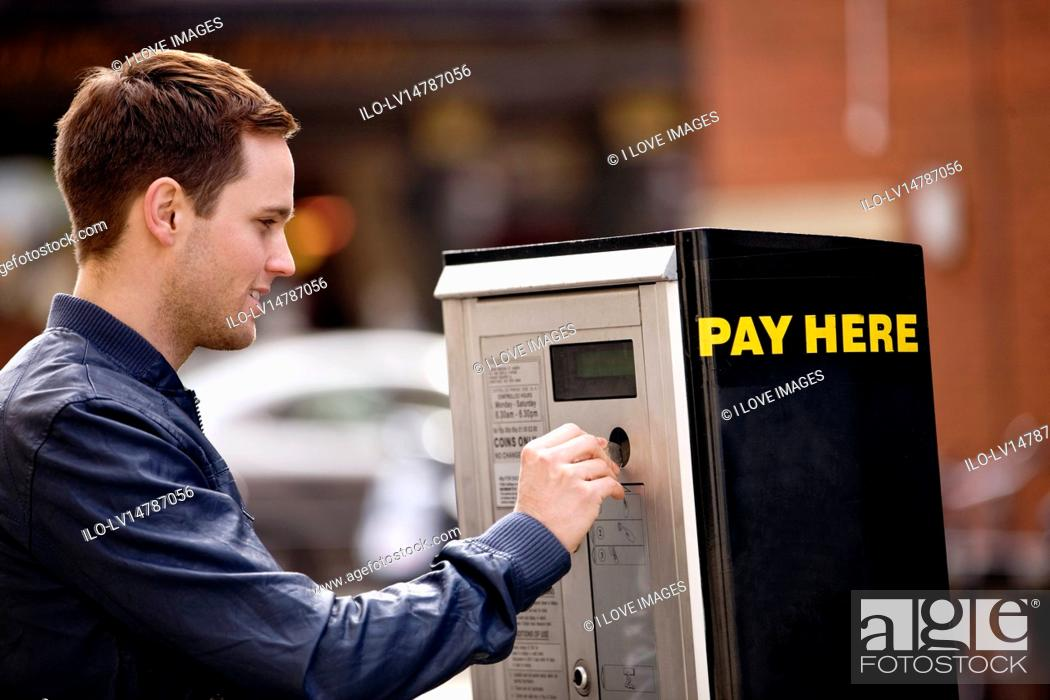 Stock Photo: A young man putting coins in a parking meter.