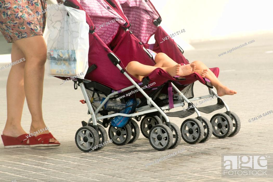 mumy dragging a cart of babies with twin bebys valencia spain