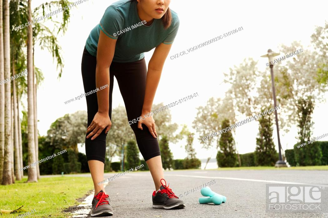 Photo de stock: tired fitness woman taking a rest after training hard on the par.