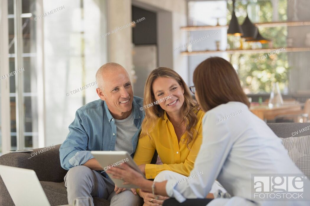 Stock Photo: Financial advisor with digital tablet meeting with couple in living room.